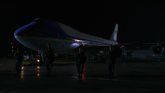 PAN LEFT TO RIGHT OF AIR FORCE ONE JET PARKED ON RUNWAY. SOLDIERS STAND AT ATTENTION AROUND PLANE NEXT TO POLICE CARS WITH LIGHTS ON.
