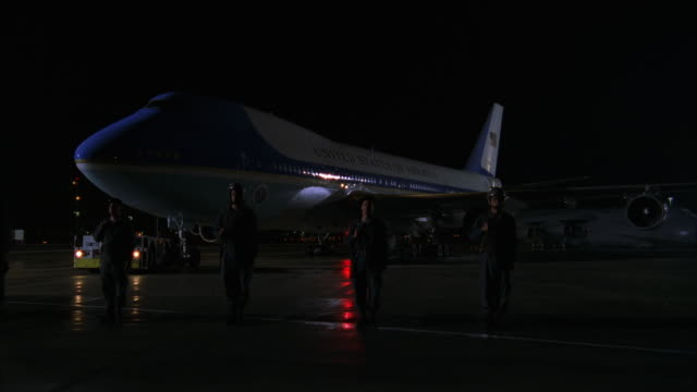pan left to right of air force one jet parked on runway. soldiers stand at attention around plane next to police cars with lights on. - エアフォースワン点の映像素材/bロール