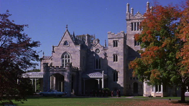 wide angle of lyndhurst mansion in tarrytown, new york. mansion is victorian era gothic revival style country villa constructed of stone. see red leaves on linden trees. - victorian stock videos & royalty-free footage