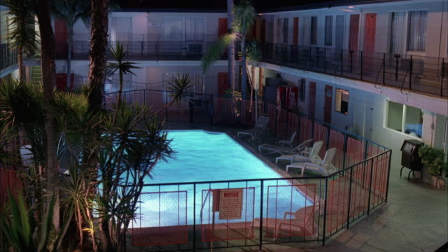 medium angle of two story motel, hotel or apartment building in square shape with courtyard with pool in center. pov from second story hallway looking across pool to other side of building. - motel stock videos and b-roll footage