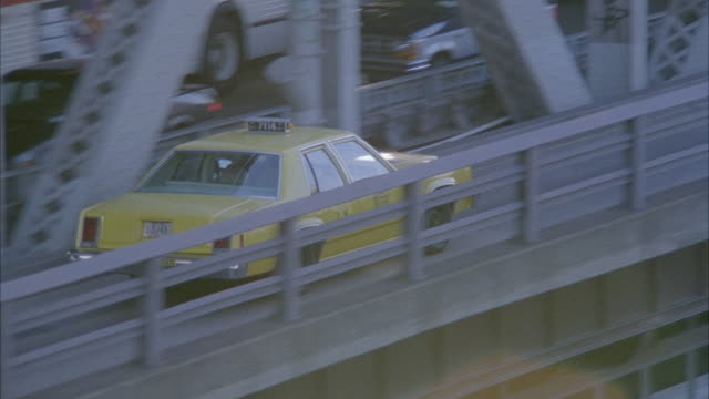 aerial tracking shot of taxi traveling eastbound on outside lane of queensboro bridge. pov pulls out and up to show bridge with new york city skyline in background. - world trade centre manhattan stock videos and b-roll footage
