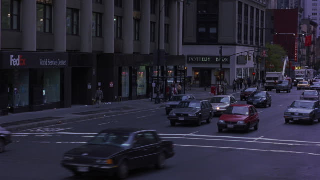 tracking shot of busy new york city street. see cars driving towards pov. see signs for pottery barn and fedex in background. see 1987 white buick lesabre weave through traffic. - 1987 stock-videos und b-roll-filmmaterial