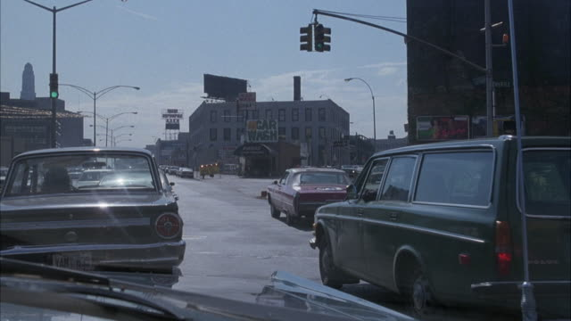 vídeos de stock, filmes e b-roll de hand held front passenger of car driving on city street in brooklyn. drives behind black ford mustang, green volvo station wagon at right, red vw volkswagen beetle drives beside pov. - 1980 1989