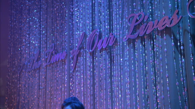 pan down from sign: the time of our lives on beaded and sparkly curtain to hotel bar with waiters serving bottled sodas and canned energy drinks only. camera moves around corner of ballroom. - beaded curtain stock videos & royalty-free footage