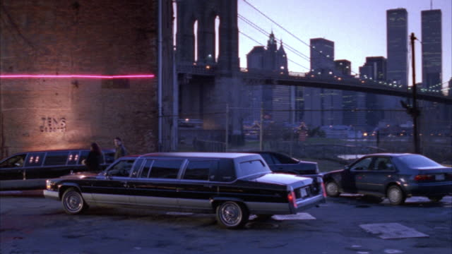 vídeos de stock e filmes b-roll de medium angle of brooklyn bridge and new york city skyline on right, see world trade center. pans left as black limo passes by parked cars and parks in front of entrance to private club in red brick building. - 1995