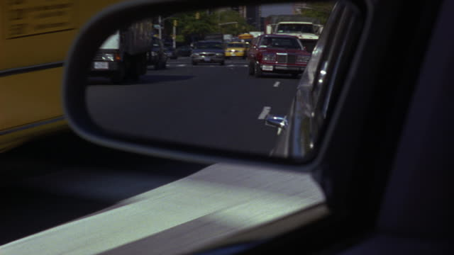 medium angle of left side mirror of white car. see car drive through city streets. see black 1995 lincoln town car and 1981 chrysler fifth avenue in mirror. see cars swerve through traffic in pursuit. looks like car chase. neg cut. chrysler car. - lincoln town car stock videos and b-roll footage
