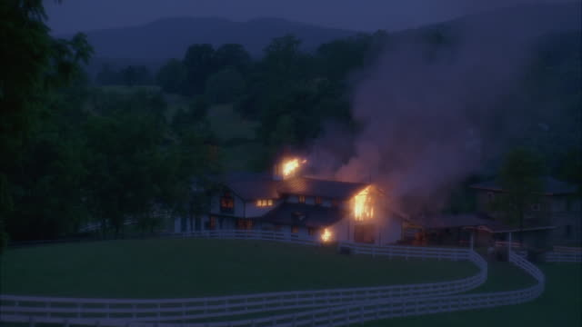 wide angle of burning stable or barn on horse farm. fire inside building, but large plume of smoke goes up and right. horse path with twin white fences leads from stable, couple walks right to left away from fire. - barn stock videos and b-roll footage
