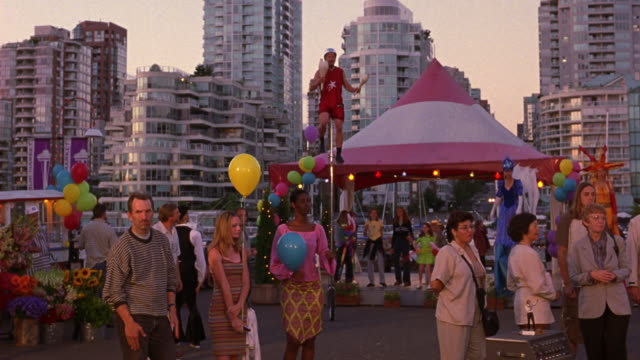 medium angle of crowd or audience at outdoor show or carnival. see crowd dancing to musical beat. see clowns, performers on stilts, and carnival acts. see single red and white tent. - anno 2001 video stock e b–roll
