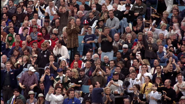 vídeos de stock e filmes b-roll de wide angle of crowd in stadium. see people cheering, standing up, clapping, and yelling. camera pans to other spectator reactions. could be football, baseball, basketball, or hockey game in sports arena. - futebol americano