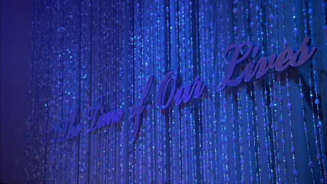 pan down from sign: the time of our lives on beaded and sparkly curtain to hotel bar with waiters serving bottled sodas and canned energy drinks only. - beaded curtain stock videos & royalty-free footage