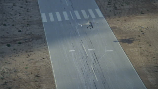 TRACKING SHOT OF A CAMOUFLAGE F-16 FIGHTER JET FLYING OVER RUNWAY IN DESERT. SEE SHADOW OF JET ON GROUND. SEE WHITE BUILDING WITH CAR PARKED OUTSIDE ON SIDE OF RUNWAY. MIDDLE EAST.