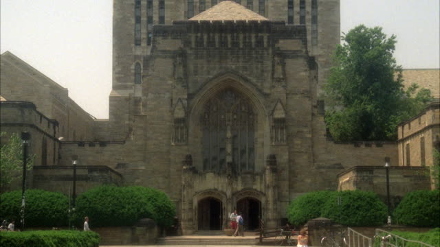wide angle of sterling memorial library at yale university. see multi-story gothic architecture. could be cathedral or church entrance. see pedestrians walking in front on plaza. ivy league college campus. - new haven stock-videos und b-roll-filmmaterial