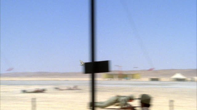 PAN RIGHT OF MILITARY BASE. SEE SOLDIERS DROP AND LAY ON GROUND AS TWO CAMOUFLAGE F-16 FIGHTER JETS FLY OVER RUNWAY IN PREPARATION FOR LANDING.