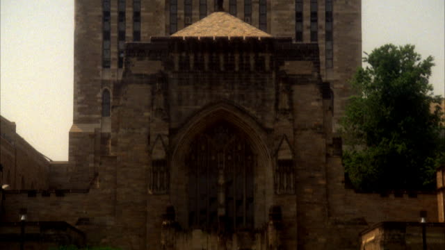 PAN DOWN OF STERLING MEMORIAL LIBRARY AT YALE UNIVERSITY. SEE MULTI-STORY GOTHIC ARCHITECTURE. COULD BE CATHEDRAL OR CHURCH ENTRANCE. SEE PEDESTRIANS WALKING IN FRONT ON PLAZA. IVY LEAGUE COLLEGE CAMPUS.