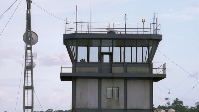 MEDIUM ANGLE OF GRAY CONCRETE THREE STORY BUILDING. LOOKS LIKE WATCH MEDIUM ANGLE OF GRAY CONCRETE THREE STORY BUILDING. AIRPORT CONTROL TOWER. METAL STRUCTURES FLANKING BUILDING.