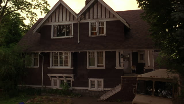 MEDIUM ANGLE OF TWO STORY TUDOR OR SHINGLE STYLE HOUSE WITH GRAY WOODEN SIDING AND WHITE TRIM. SEE GABLED WINDOWS ON SECOND FLOOR WITH STRIPED PATTERN. SEE LARGE STONE BASEMENT VISIBLE UNDERNEATH FIRST FLOOR.