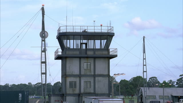 MEDIUM ANGLE OF GRAY CONCRETE THREE STORY BUILDING. AIRPORT CONTROL TOWER. METAL STRUCTURES FLANKING BUILDING. COULD BE RADAR ANTENNAE. MILITARY AIRBASE. SEE FOREST IN BACKGROUND. CUMULUS CLOUDS. ZOOM TO TWO MEN IN CONTROL TOWER.