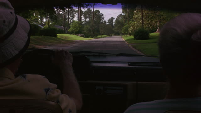 medium angle driving or moving pov from rear interior of station wagon. see elderly couple in front seats. see car drive down two lane road lined with tall full trees. looks like country road through upper middle class residential area. - 1993 stock-videos und b-roll-filmmaterial