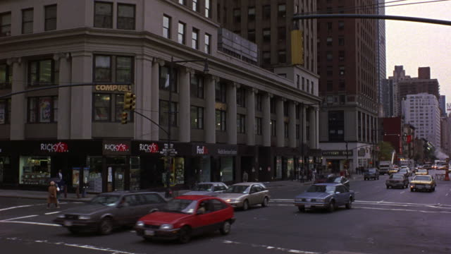 TRACKING SHOT OF BUSY NEW YORK CITY STREET. SEE CARS DRIVING TOWARDS POV. SEE SIGNS FOR POTTERY BARN AND FEDEX IN BACKGROUND. SEE 1987 WHITE BUICK LA SABRE WEAVE THROUGH TRAFFIC.