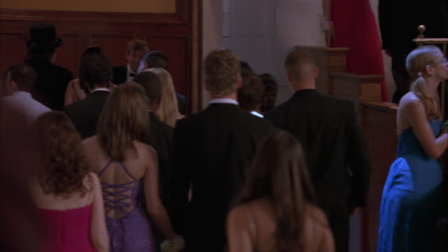 pan left to right of teenagers, high school students or couples wearing evening gowns and tuxedos at school prom, dance, party or celebration in ballroom or hotel. - ballroom stock videos & royalty-free footage