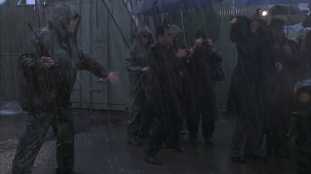 wide angle of soldiers standing guard outside fence in rain. see reporters to right side under umbrellas trying to get past soldiers. soldiers block reporters from getting by as hummer suv drives from right to left through fence. - military camp stock videos & royalty-free footage