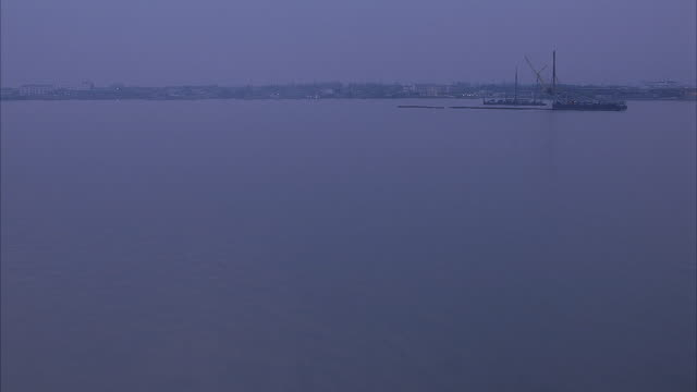aerial of coastal town with heavy dark fog. pov  crosses large body of water and shipyard with boats and ships on docks. industrial area, then see upper income tract housing communities divided by trees and farmlands. - tract housing stock videos and b-roll footage