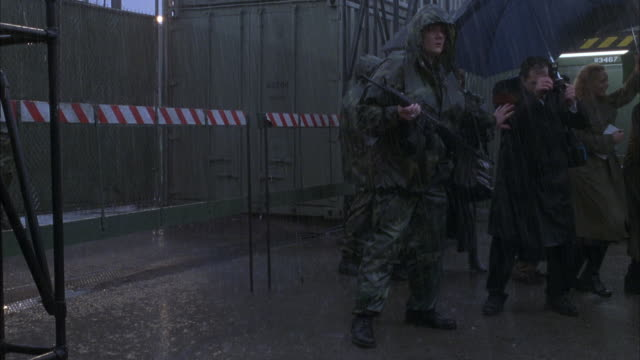 wide angle of soldiers standing guard outside fence in rain. see reporters to right side under umbrellas trying to get past soldiers. soldiers block reporters from getting by as hummer suv drives from right to left through fence. - hummer stock videos & royalty-free footage