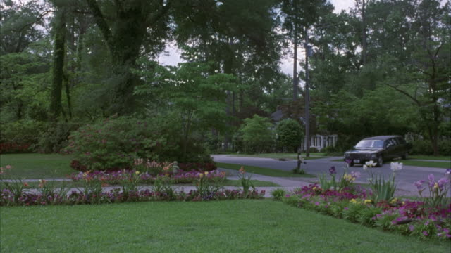 MEDIUM ANGLE OF UPPER CLASS NEIGHBORHOOD RESIDENTIAL STREET. SEE MANICURED LAWN IN FOREGROUND SURROUNDED BY VARIOUS SHRUBS AND FLOWERS. SEE BLACK 1993 CADILLAC FLEETWOOD PARKED HALFWAY ONTO SIDEWALK ON FAR SIDE OF STREET.