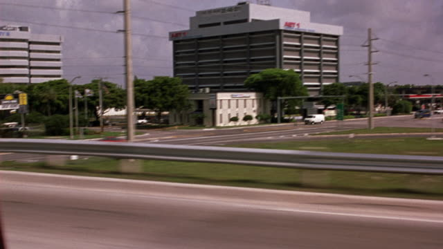 driving pov on highway from passenger side. passes exit ramp and zooms in on six story office building. see palm trees in front of days inn hotel. - inn stock videos and b-roll footage
