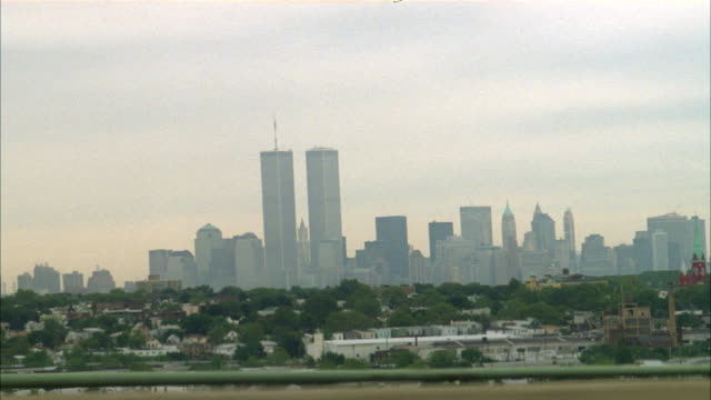 PROCESS PLATE OF DRIVER'S SIDE VIEW OF EXPRESSWAY IN NEW JERSEY LOOKING TOWARD LOWER MANHATTAN AND THE WORLD TRADE CENTER TWIN TOWERS. SEE HAZY BLUE SKY. SEE SUBURBAN NEW JERSEY TOWN.