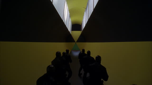 WIDE ANGLE OF LONG YELLOW AND BLACK FUTURISTIC HALLWAY OR TUNNEL. PATTERN ON WALL COULD BE RADIATION HAZARD WARNING SIGN. SEE WINDOWS ABOVE.