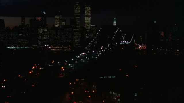 high angle down of new york skyline and brooklyn bridge. pans left over sunset to lights from high rise office buildings and the headlights and taillights of cars on various freeways. - 1989 stock videos and b-roll footage