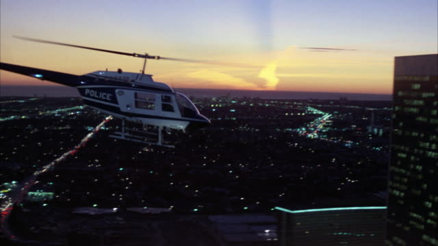 medium angle tracking shot of police helicopter flying right across los angeles or century city skyline. see sunset hues of pink and purple in far background. skyscrapers or office buildings. - century city stock videos & royalty-free footage