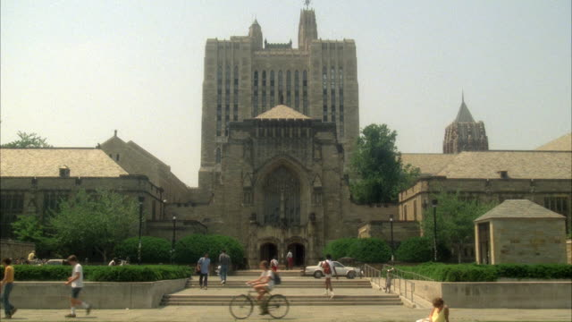 WIDE ANGLE OF STERLING MEMORIAL LIBRARY AT YALE UNIVERSITY. SEE MULTI-STORY GOTHIC ARCHITECTURE. COULD BE CATHEDRAL OR CHURCH ENTRANCE. SEE PEDESTRIANS WALKING IN FRONT ON PLAZA. IVY LEAGUE COLLEGE CAMPUS.