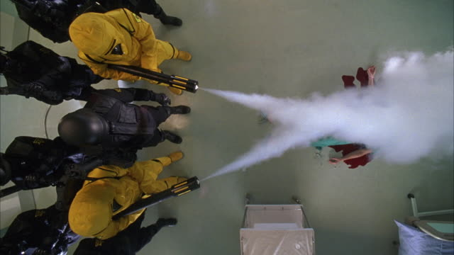 high angle down of armed soldiers in black uniforms and masks with two firemen in yellow uniforms spraying fire extinguishers toward dead body. see blood on floor surrounding body. - fire extinguisher stock videos & royalty-free footage