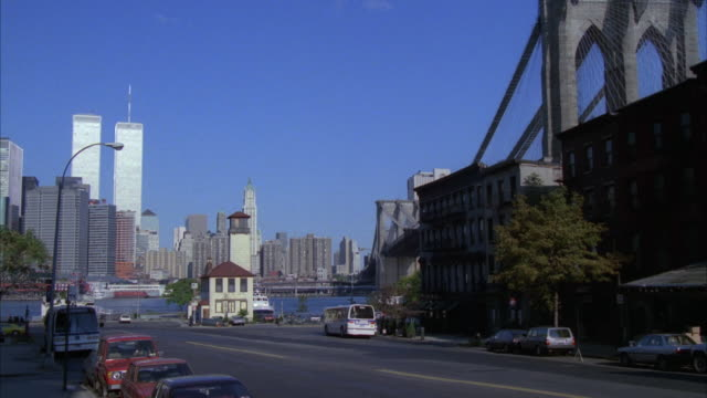 wide angle of new york city skyline. see twin towers. see cars and city buses driving on street in front of manhattan harbor. see bridge at right, cars parked along street and buildings on right. - 1989 bildbanksvideor och videomaterial från bakom kulisserna