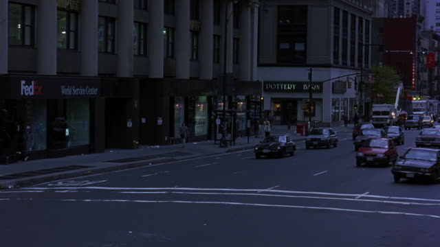 TRACKING SHOT OF BUSY NEW YORK CITY STREET. SEE CARS DRIVING TOWARDS POV. SEE SIGNS FOR POTTERY BARN AND FEDEX IN BACKGROUND. SEE 1987 WHITE BUICK LESABRE WEAVE THROUGH TRAFFIC.