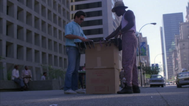 up angle pov of sidewalk street vendor with makeshift stand or table made of cardboard boxes selling sunglasses to another man. see two women sitting on ledge in left background - makeshift stock videos and b-roll footage