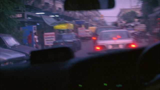 medium angle of pov inside a car driving down a rundown, busy city street lined with small shops, markets, vendors, parked motorcycles, cars, multi-story buildings, and people. - bangkok stock-videos und b-roll-filmmaterial