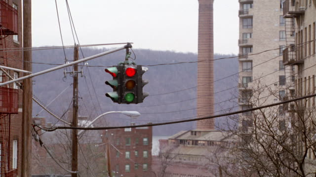 MEDIUM ANGLE OF TRAFFIC SIGNAL WITH RED SIGNAL LIT. SEE APARTMENT BUILDINGS ON RIGHT AND LEFT SIDES. SEE PHONE AND ELECTRICAL LINES ACROSS SCREEN.