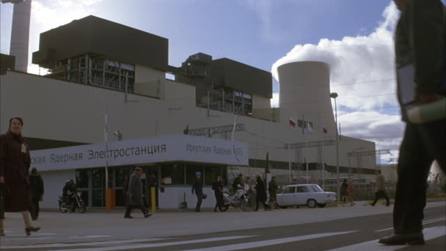 medium angle of nuclear power plant. camera moves to see close up of entrance. see sign in russian on top of entrance of factory. see people and cars pass through gated entrance guarded by armed security guards or soldiers. - nuclear power station stock videos & royalty-free footage