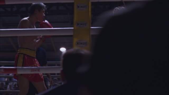 medium angle of kickboxers fighting in boxing ring from outside ring pov. men in ring punching and kicking each other. man on left in red shorts. - muay thai stock videos and b-roll footage