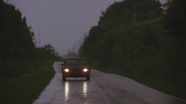 MEDIUM ANGLE OF 1992 RED CHEVROLET LUMINA FOLLOWING POV DURING RAIN STORM ON COUNTRY ROAD. COULD BE REAR DRIVING PROCESS PLATE. HEADLIGHTS ARE TURNED ON AND WINDSHIELD WIPERS.