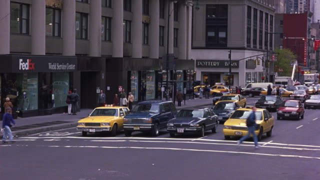 TRACKING SHOT OF BUSY NEW YORK CITY STREET. SEE TRAFFIC MOVING IN BACKGROUND. SEE RED 1981 CHRYSLER FIFTH AVENUE WEAVE THOUGH STOPPED CARS.  SEE SIGNS FOR POTTERY BARN AND FEDEX IN BACKGROUND.