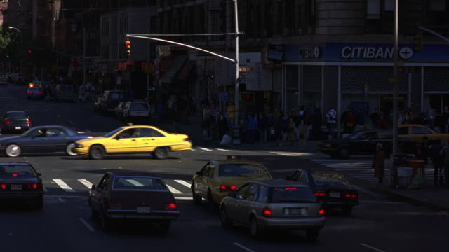 medium angle of new york city street corner. see cars driving on street and pedestrians on sidewalk. see various vehicles including taxies. - red light stock videos & royalty-free footage