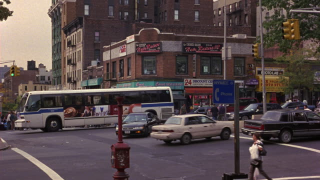 MEDIUM ANGLE OF NEW YORK CITY STREET INTERSECTION. SEE TRAFFIC ON INTERSECTION. SEE PEDESTRIANS CROSSING STREET WALKWAYS. SEE RED BRICK APARTMENT BUILDING IN BACKGROUND. SEE BLUE PHONE BOOTH SIGN IN FOREGROUND.