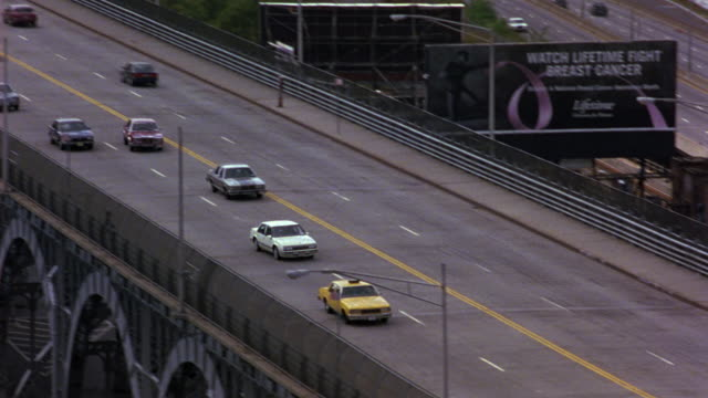 high angle down of curving four lane street along hudson river. could be riverside drive in brooklyn. see thick nonconiferous trees lining hill alongside road. see river at right. - 1981 stock-videos und b-roll-filmmaterial