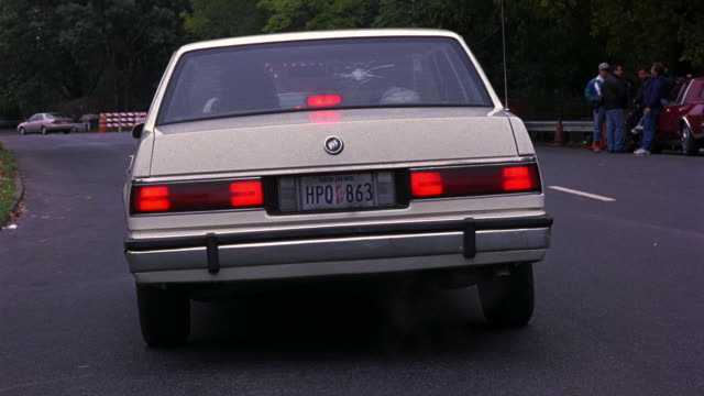 medium angle of white buick le sabre car on two lane road. car is facing away from pov. see bullet hole in rear window. see construction cones along road on right. - acrobazia video stock e b–roll