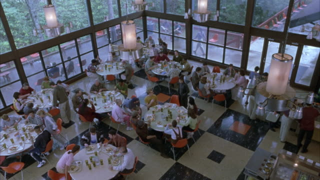 high angle down of cafeteria or restaurant. see customers or guests holding white trays of food. see guests sit at round white plastic tables at orange plastic chairs. see buffet line at right. - canteen stock videos & royalty-free footage