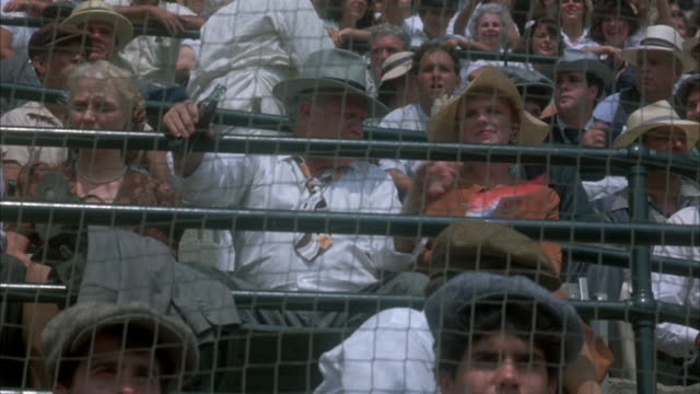MEDIUM ANGLE. CROWD SITS AT STADIUM WATCHING BASEBALL GAME. POV FROM BEHIND FENCE ON FIELD. UP ANGLE OF CROWD. VENDOR IN WHITE UNIFORM SELLS OUT OF BOX. PEOPLE IN CROWD FAN THEMSELVES, TALK.